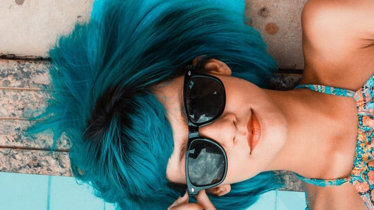Woman with Teal Hair, coral colored lipstick and sunglasses lying on a brick border next to a pool