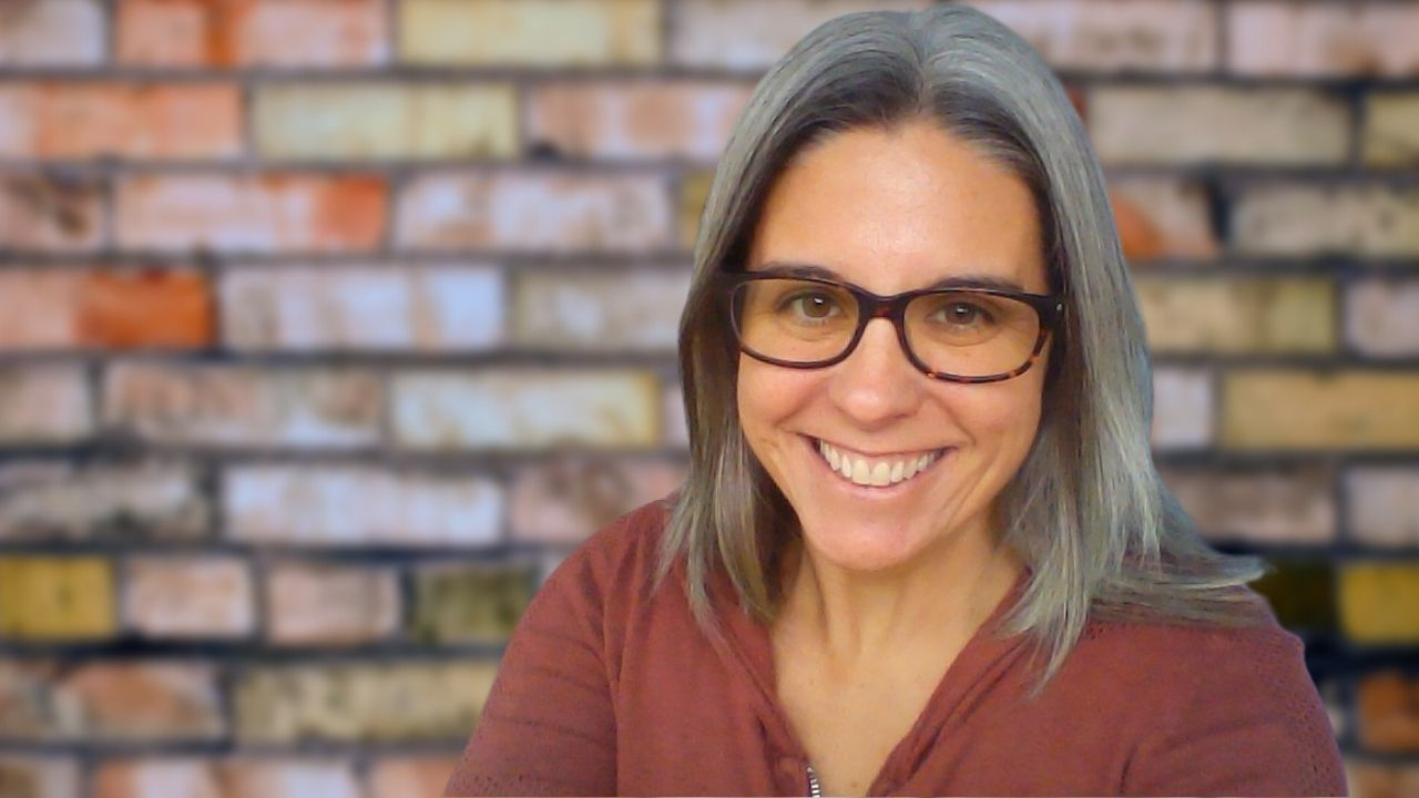 Karisa Prestera - Woman with grey hair and glasses smiling in front of a brick wall
